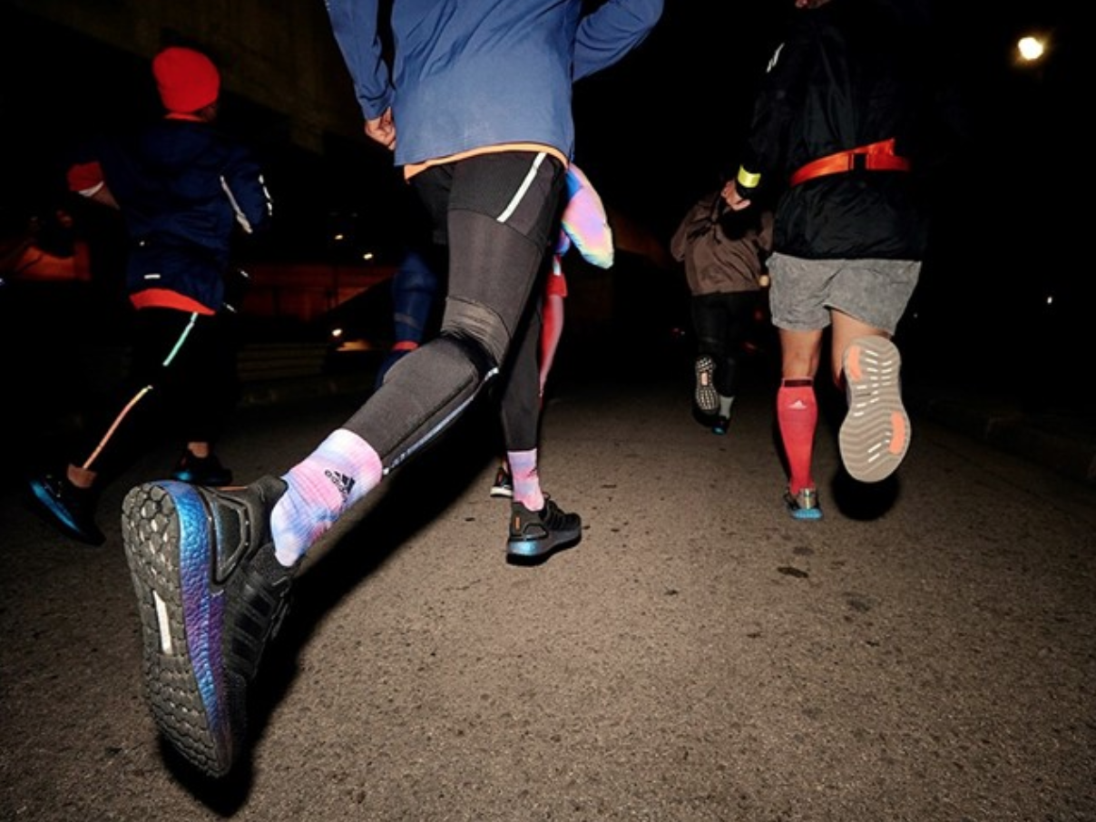 A group of athletes run in Adidas' new UltraBoost 20 sneakers.