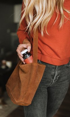 Women pulling out a supplement bottle from her leather tote bag.