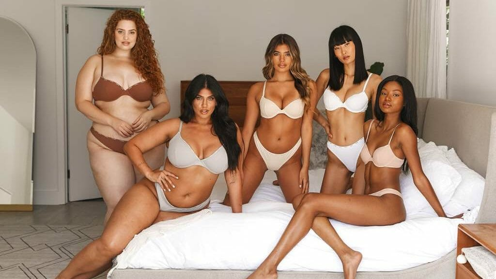 An advertisement for top lingerie brand Lounge Underwear, featuring five female models on a bed.