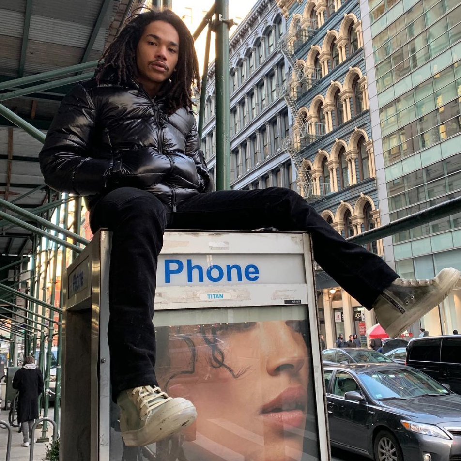 Luka Sabbat sits on a phone booth