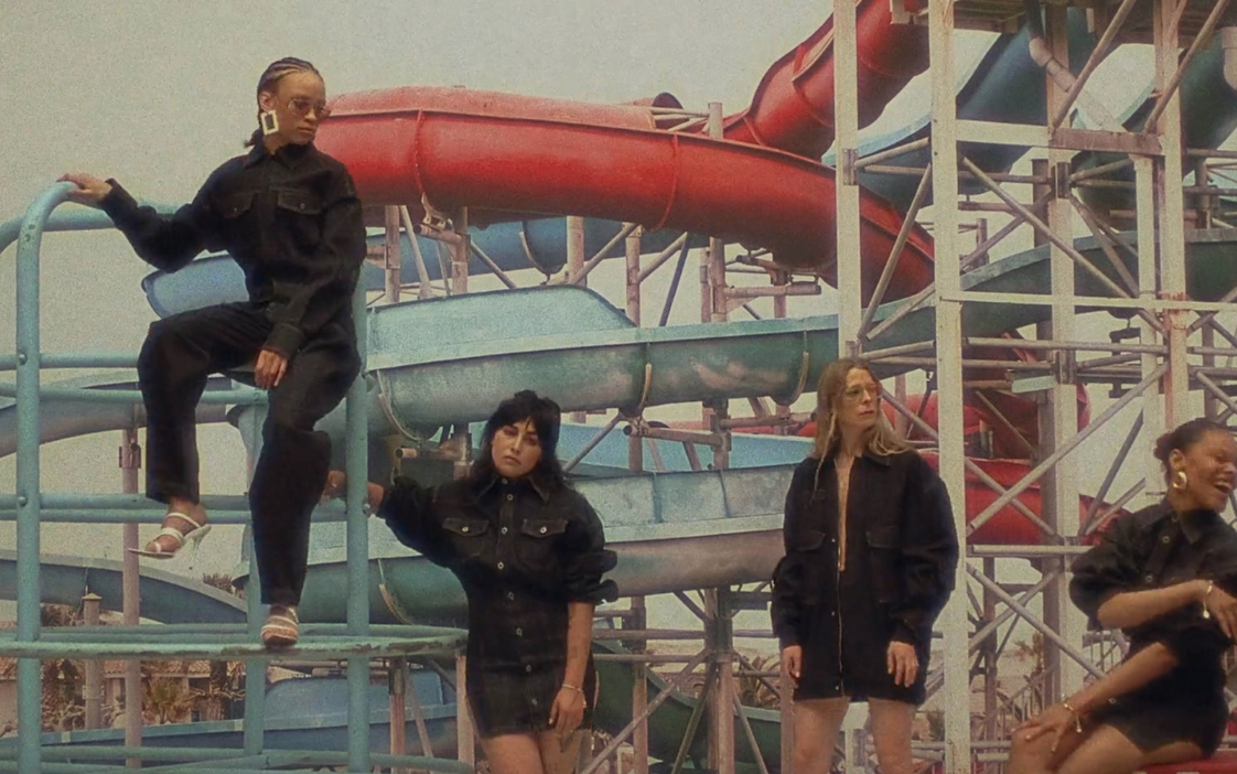 Four women lounge at a water park in Fenty apparel.