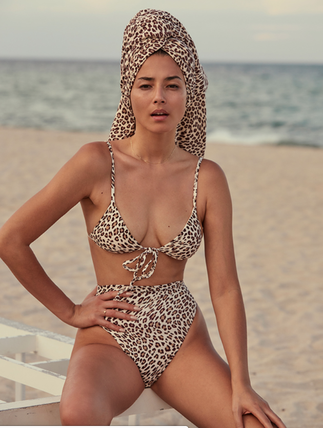 A woman in a leopard print bikini from Monday Swimwear sits on a beach.