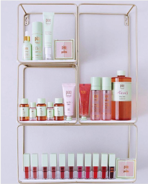 A photo of several shelves full of Pixi Beauty products.