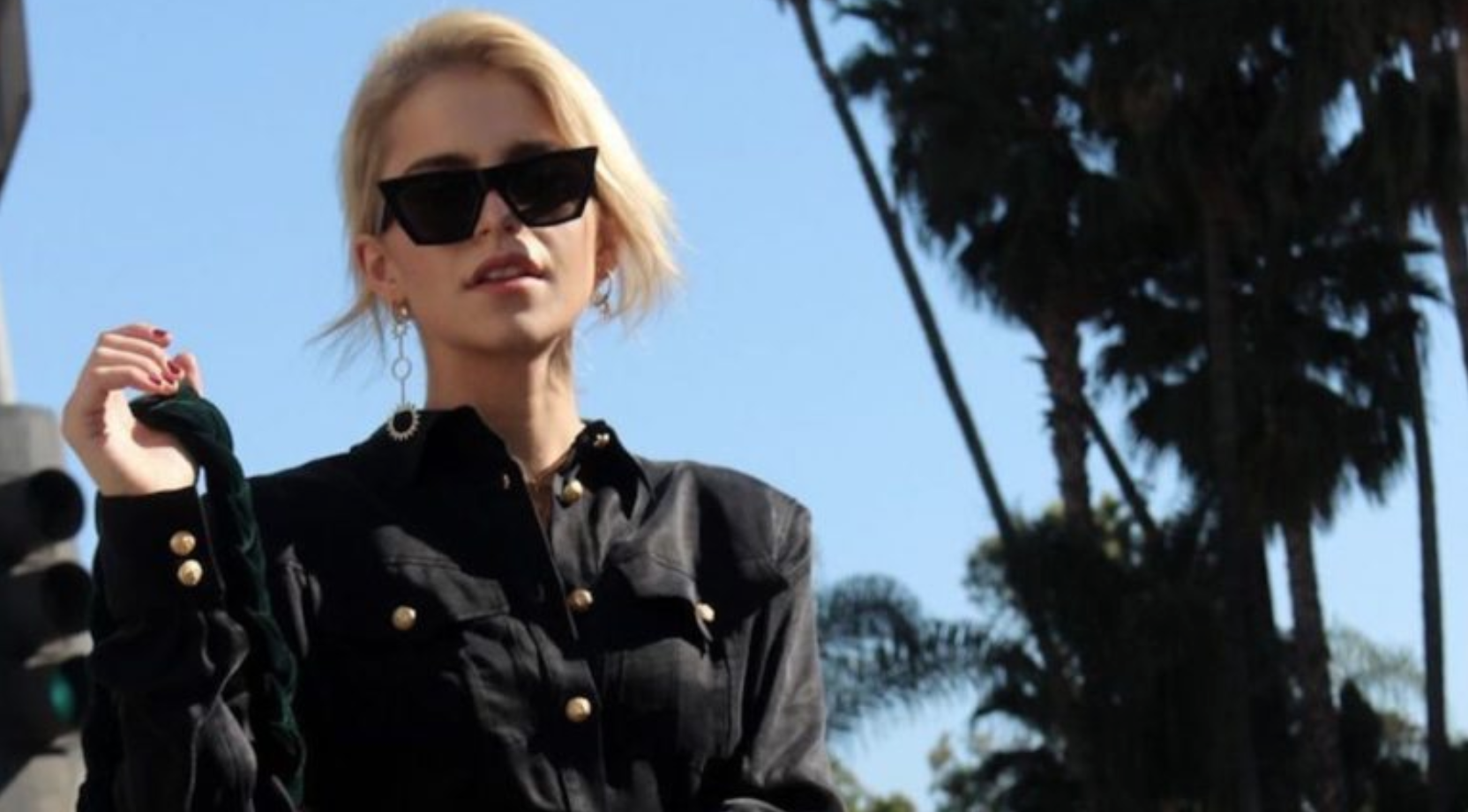 Caroline Daur walks past palm trees in black sunglasses and a leather jacket.