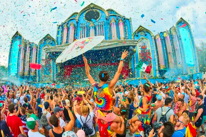 Tomorrowland festival attendees raise their hands amid confetti.