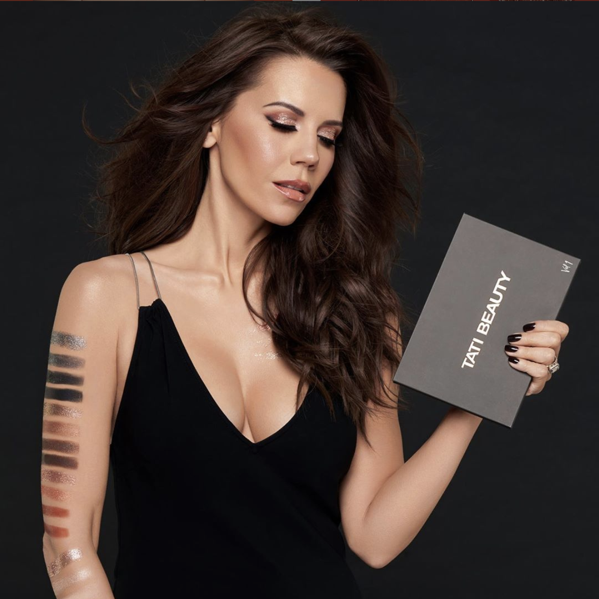 An advertisement for Tati Beauty's Textured Neutrals Vol 1 eyeshadow palette, featuring Tati Westbrook holding the palette with eyeshadow swatches down her arm.