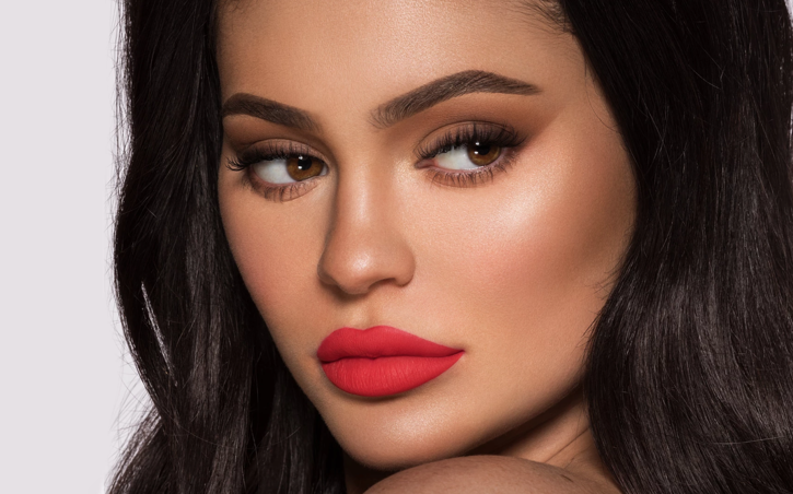 A close-up photograph of Kylie Jenner wearing products from her namesake Kylie Cosmetics brand.