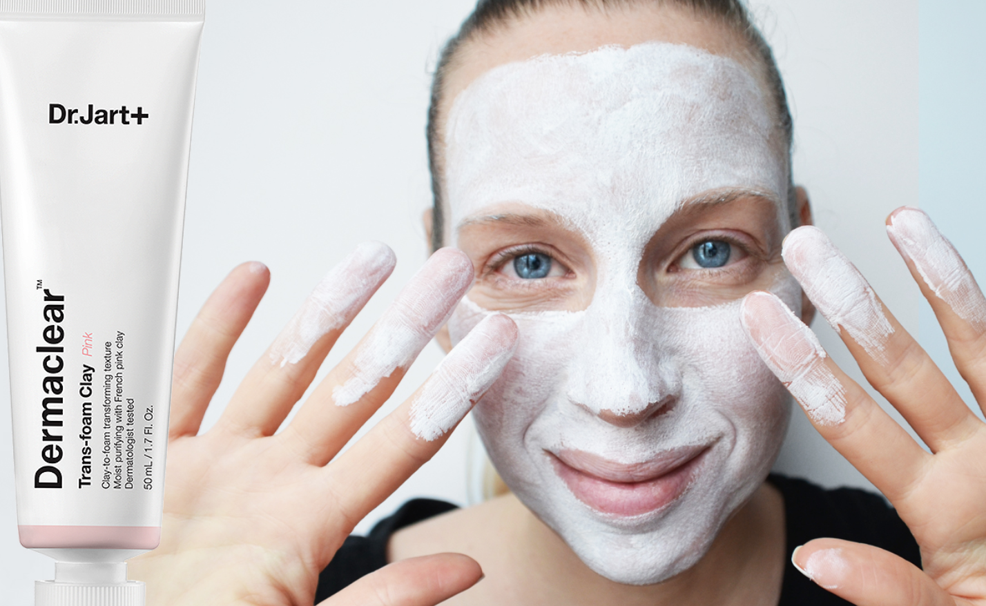 An influencer wearing a white clay face mask holds his hands up next to a bottle of Dr.Jart+'s Dermaclear Trans-foram Clay.