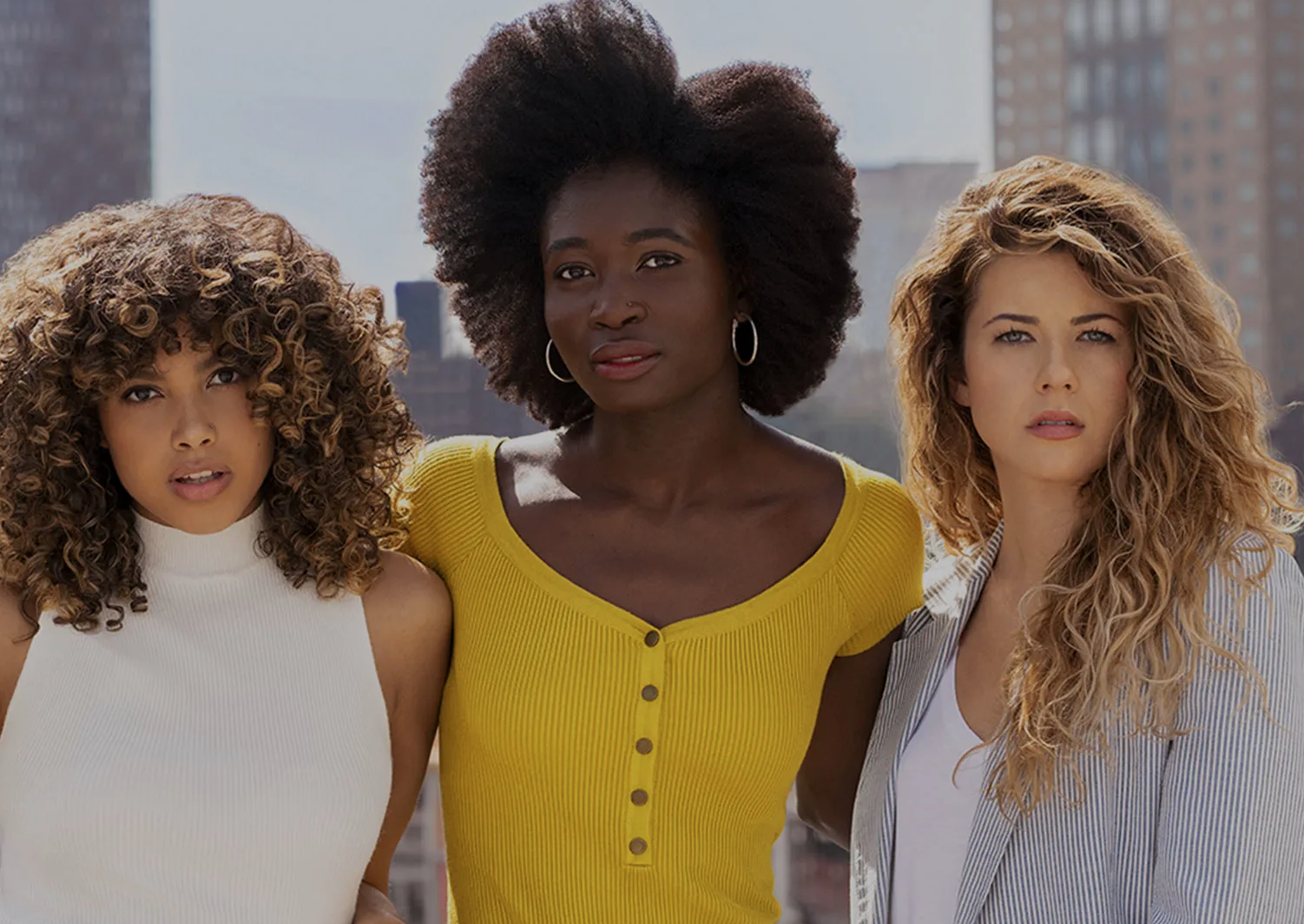 Three curly-haired models pose in an advertisement for DevaCurl.