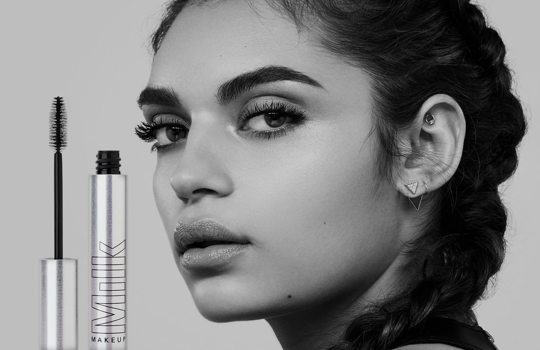 An advertisement for Milk Makeup's Kush Mascara featuring a model and a close-up shot of the product.
