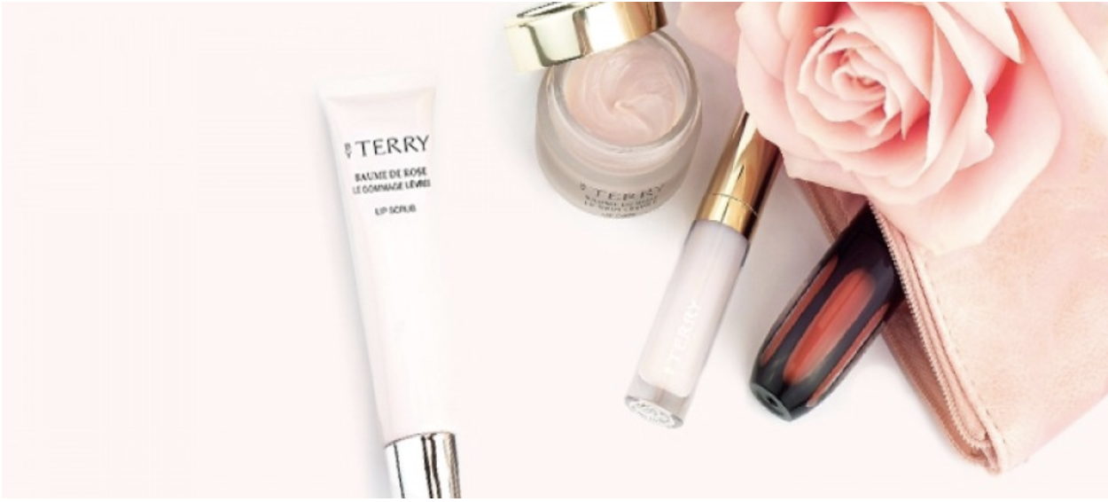 A flat-lay photo featuring ByTerry's Baume de Rose Lip Scrub and Face Cream.