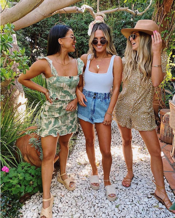A trio of women wearing Show Me Your Mumu outfits outside.
