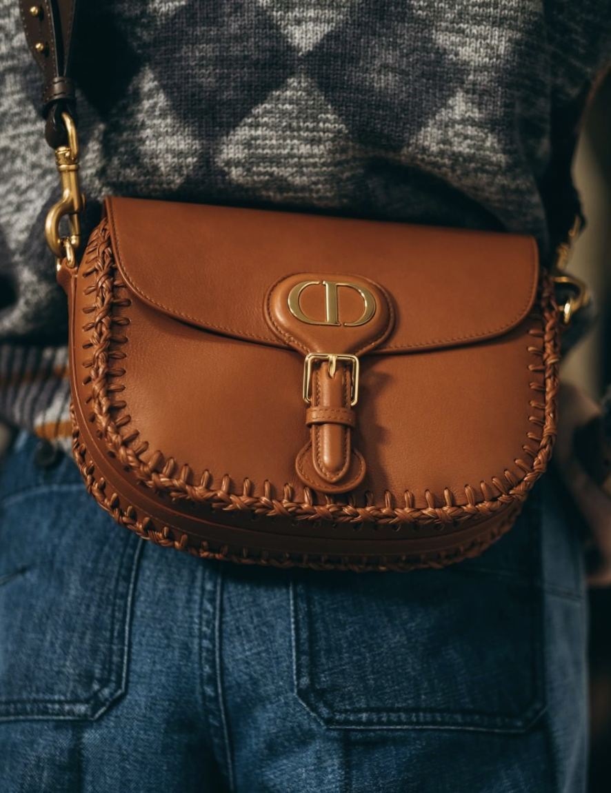 A close-up photo of a person wearing Dior's Bobby Bag.