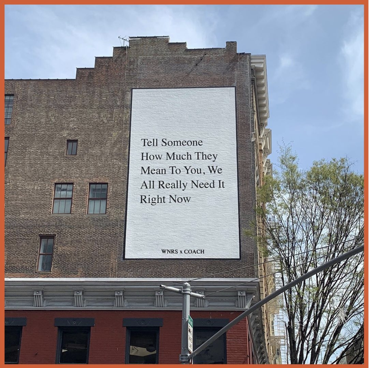 """A brick building with the message """"Tell Someone How Much They Mean To You, We All Really Need it Right Now"""" painted on it as part of Coach's partnership with We're Not Really Strangers."""