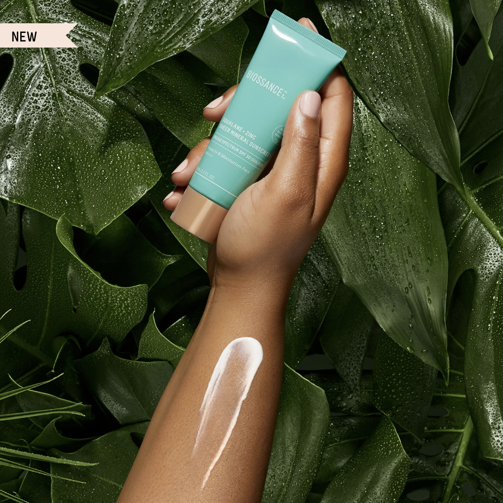 An advertisement for Biossance's Squalene + Zinc Sheer Mineral Sunscreen, featuring a person holding the product amid greenery.