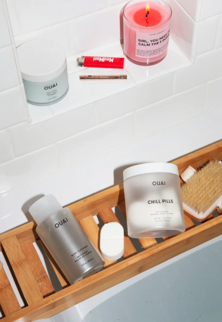 A flat-lay of several bath products, including Ouai's Chill Pills and Body Cleanser.