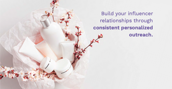 "A photo of a package of products, pink and white flowers, and white tissue paper with the sentence ""Build your influencer relationships through consistent personalized outreach"" superimposed in purple text."