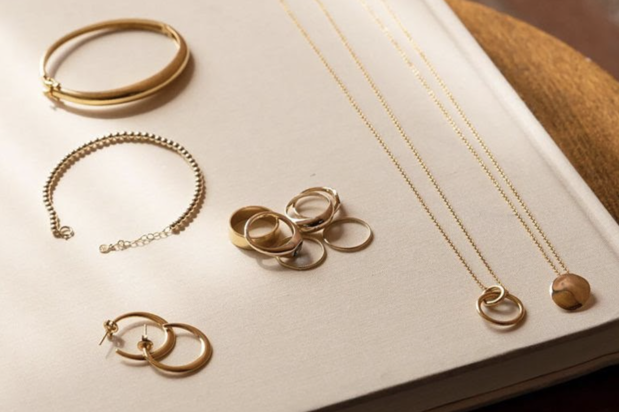 Mejuri jewelry arranged on a white surface.