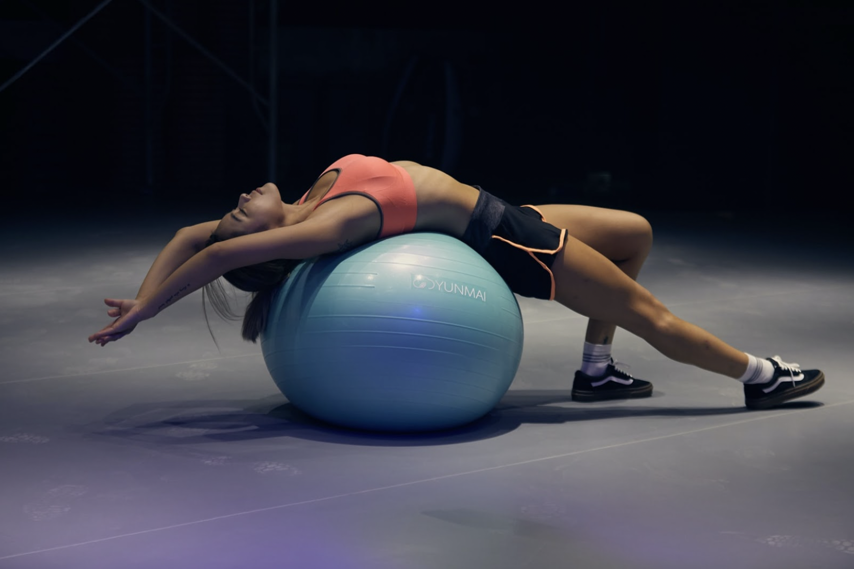 A fitness influencer in apparel from an activewear brand on an exercise ball.