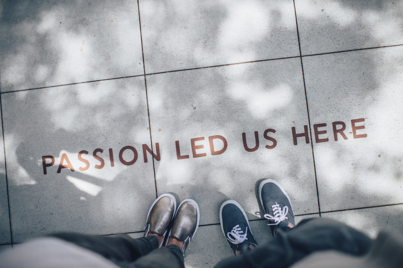 """A photo by Ian Schneider, featuring the shoes of two individuals standing next to a sign on the ground that reads """"Passion Led Us Here."""""""