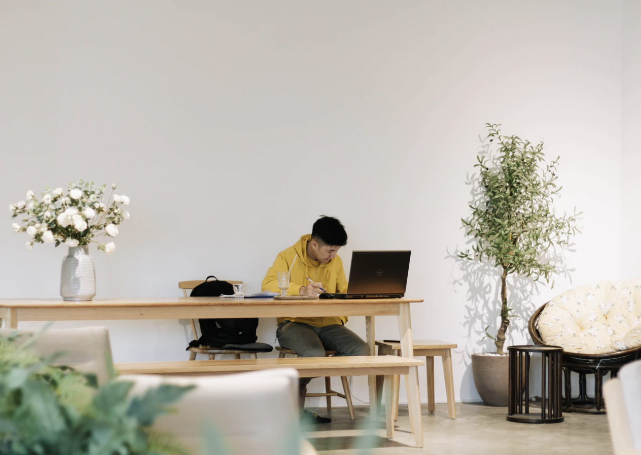 A photo by Nguyen Dang Hoang Nhu featuring a man working at a desk with flowers.