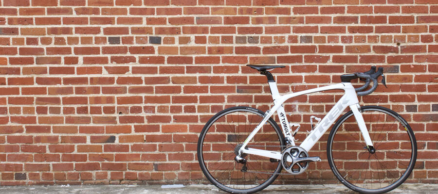 A white TREK Madone in front of a brick wall.
