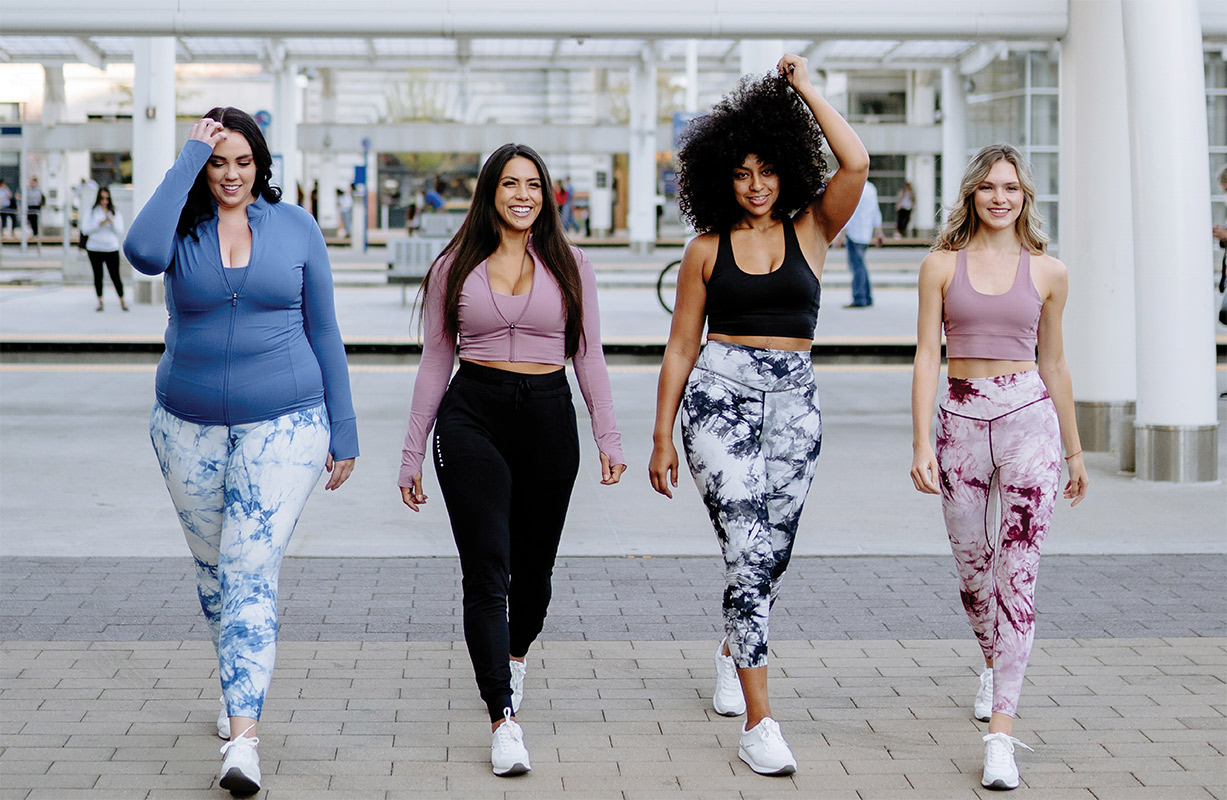 Four women model Balance Athletica athleisure sets in a public walkway.