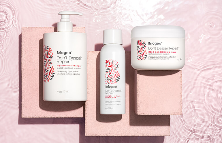 Products from Briogeo's Don't Despair, Repair! Collection displayed against a pale pink background.