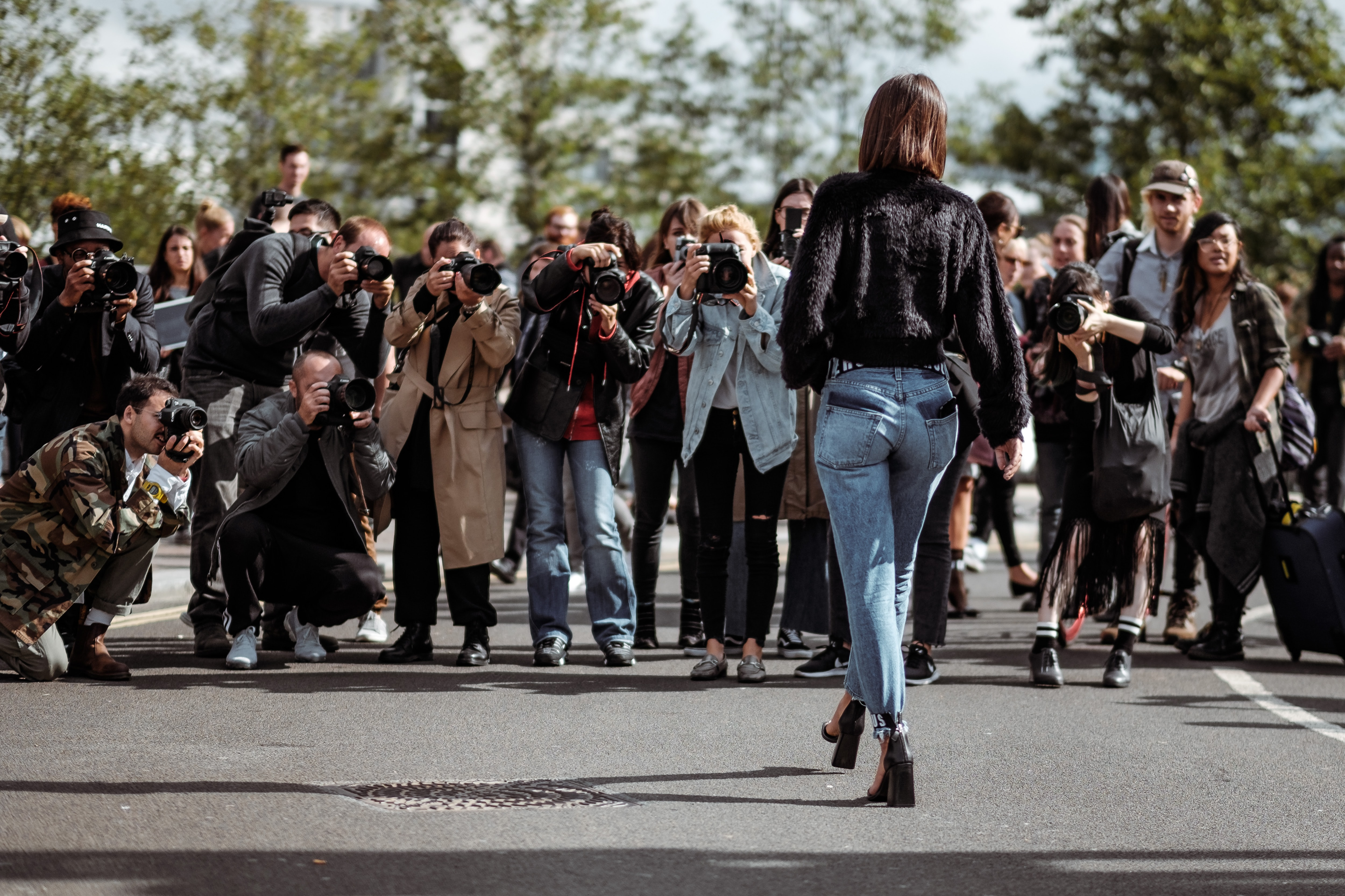 A photo of a woman from behind being photographed by a large group of photographers.