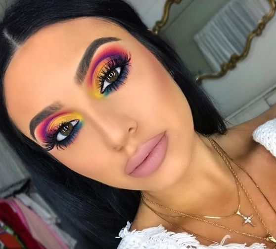 An influencer shows off a colorful cut-crease in her bedroom.