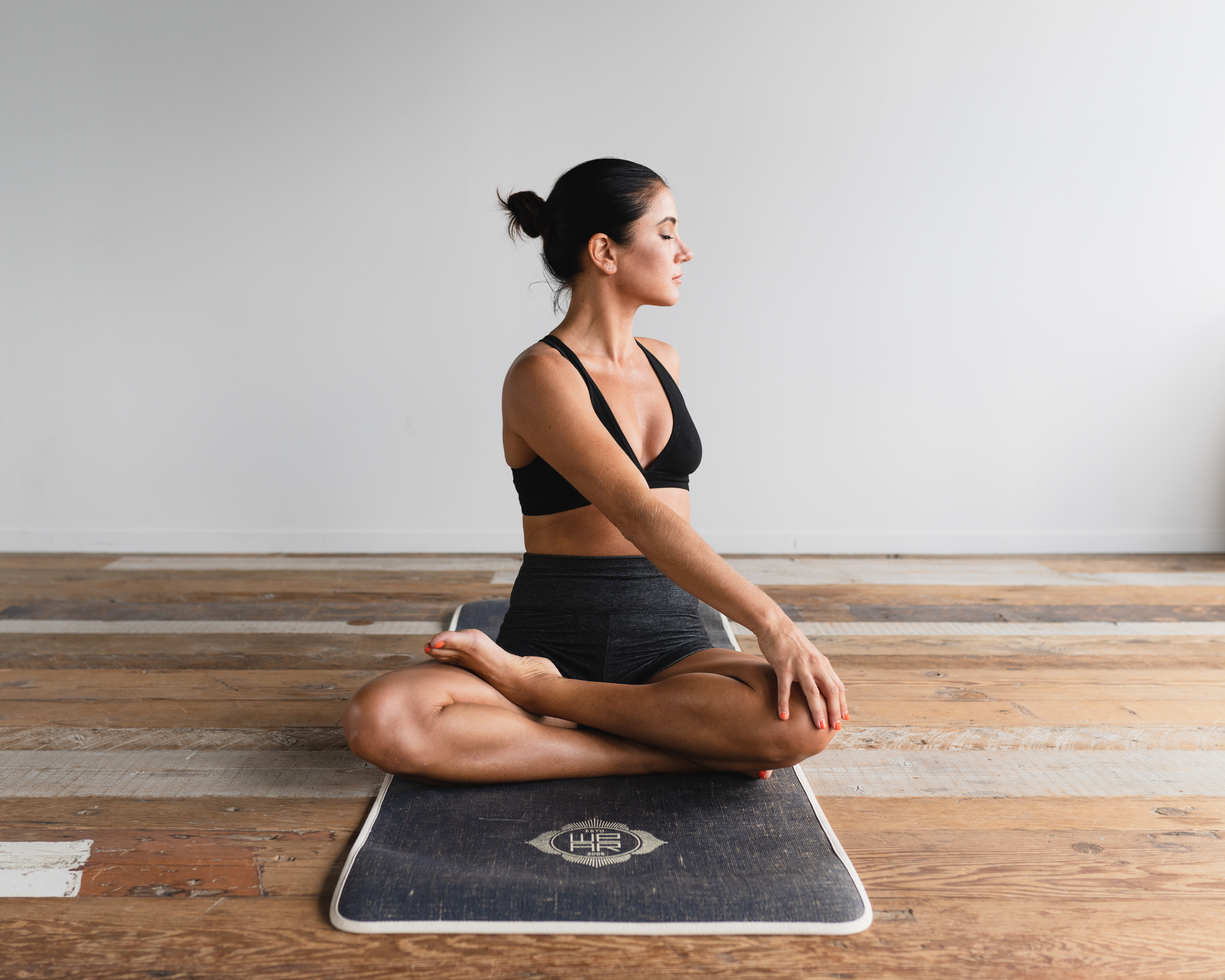 A woman doing yoga on a mat indoors.