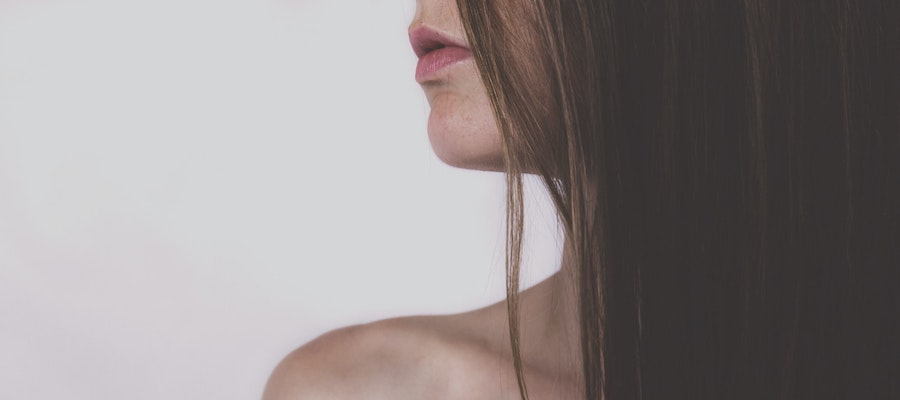 A profile of a bare-shouldered woman with long brown hair, from freestocks.