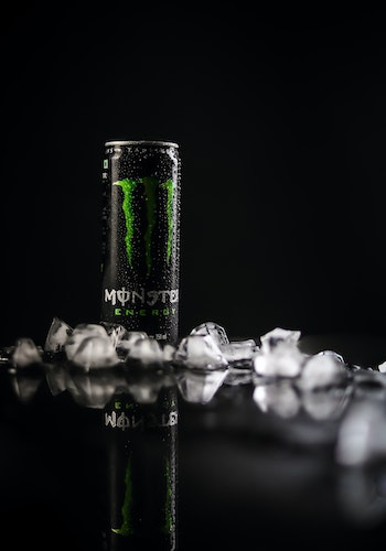 A can of Monster Energy drink surrounded by ice cubes against a black background, by Gkphotography 53.