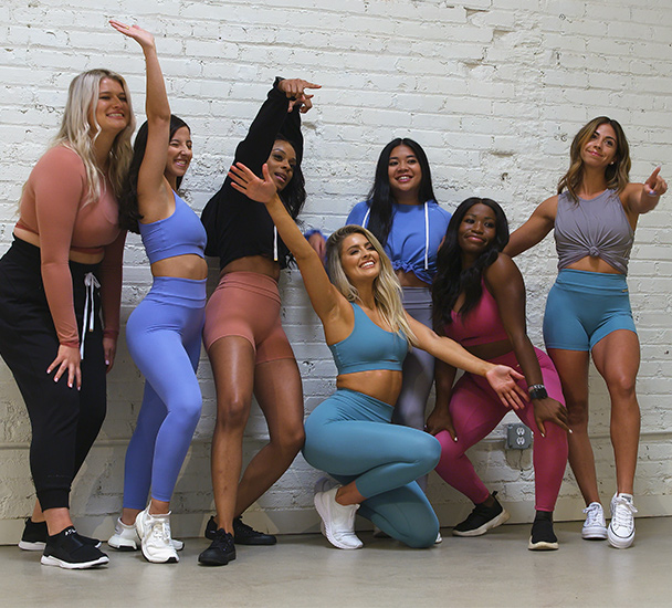 Fitness influencers wearing the Gymshark x Whitney Simmons athleisure collection pose against a white brick wall.