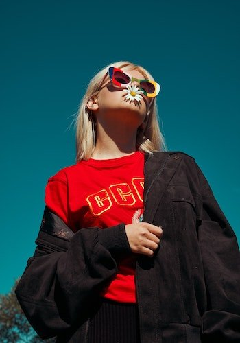 A gen z fashion influencer wearing colorful sunglasses, by Katsiaryna Endruszkeiwicz.