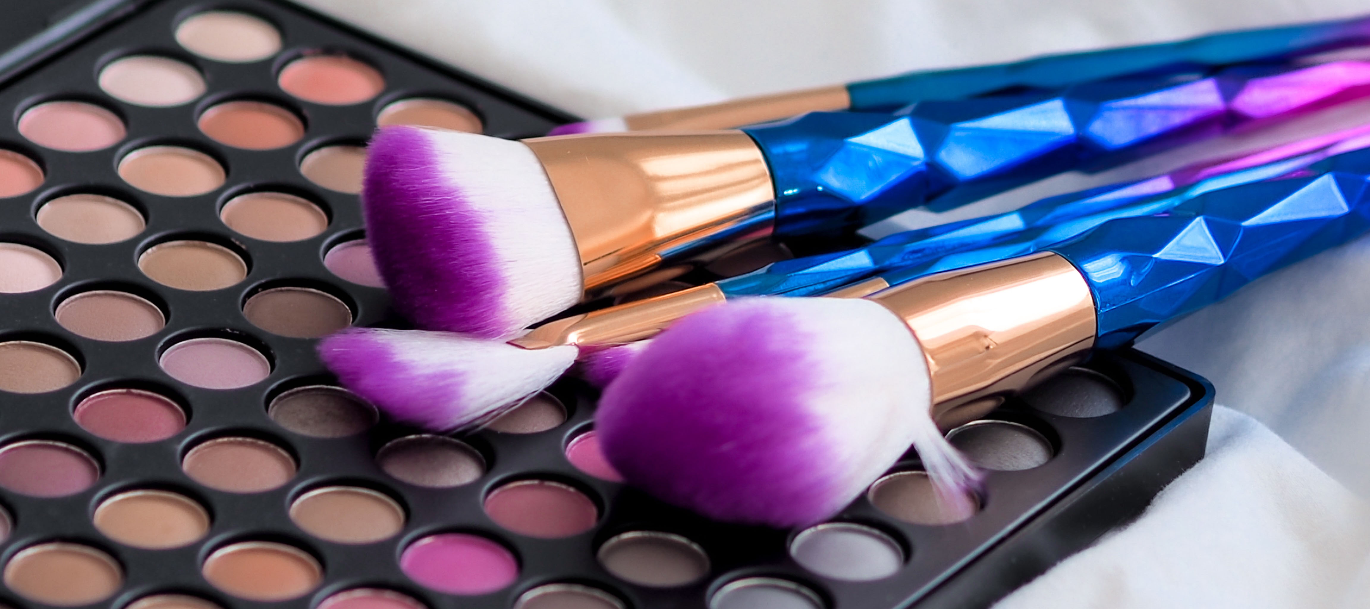 Cosmetic brushes on a colorful makeup palette.