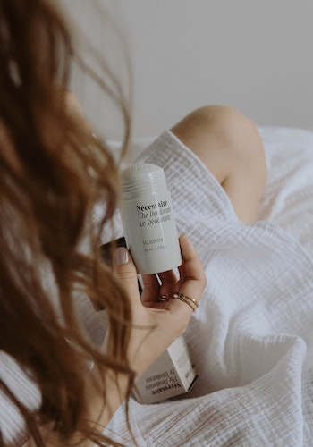 A woman holding deodorant from clean beauty brand Nécessaire, by Mathilde Langevin.