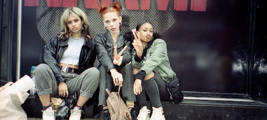 Three fashion influencers seated outside an event venue, by Matt Moloney.