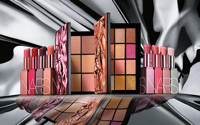 NARS' Afterglow collection of eye, lip, and complexion products arranged in front of a silver background.