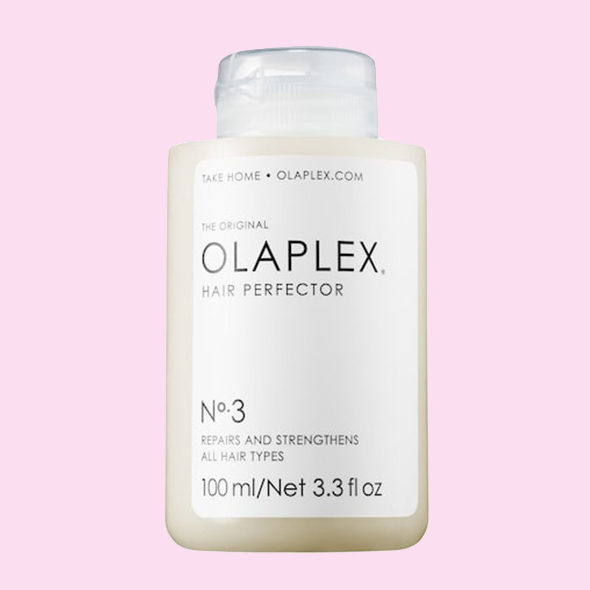 A bottle of Olaplex's No. 3 Hair Perfector displayed against a pink background.