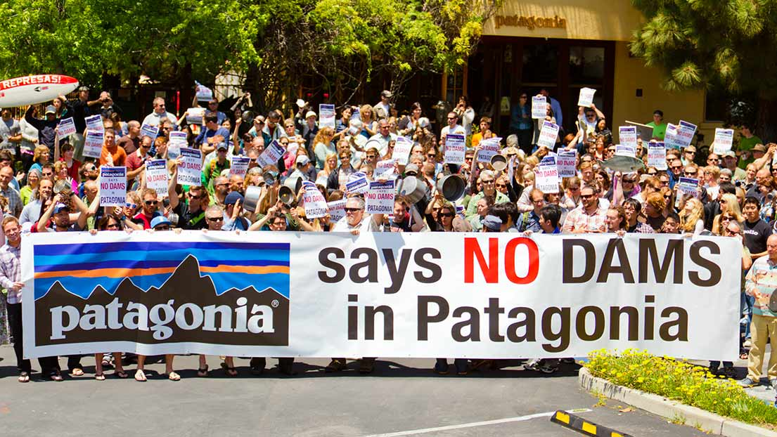 "Patagonia employees protest with a sign that reads ""Patagonia says no dams in Patagonia."""