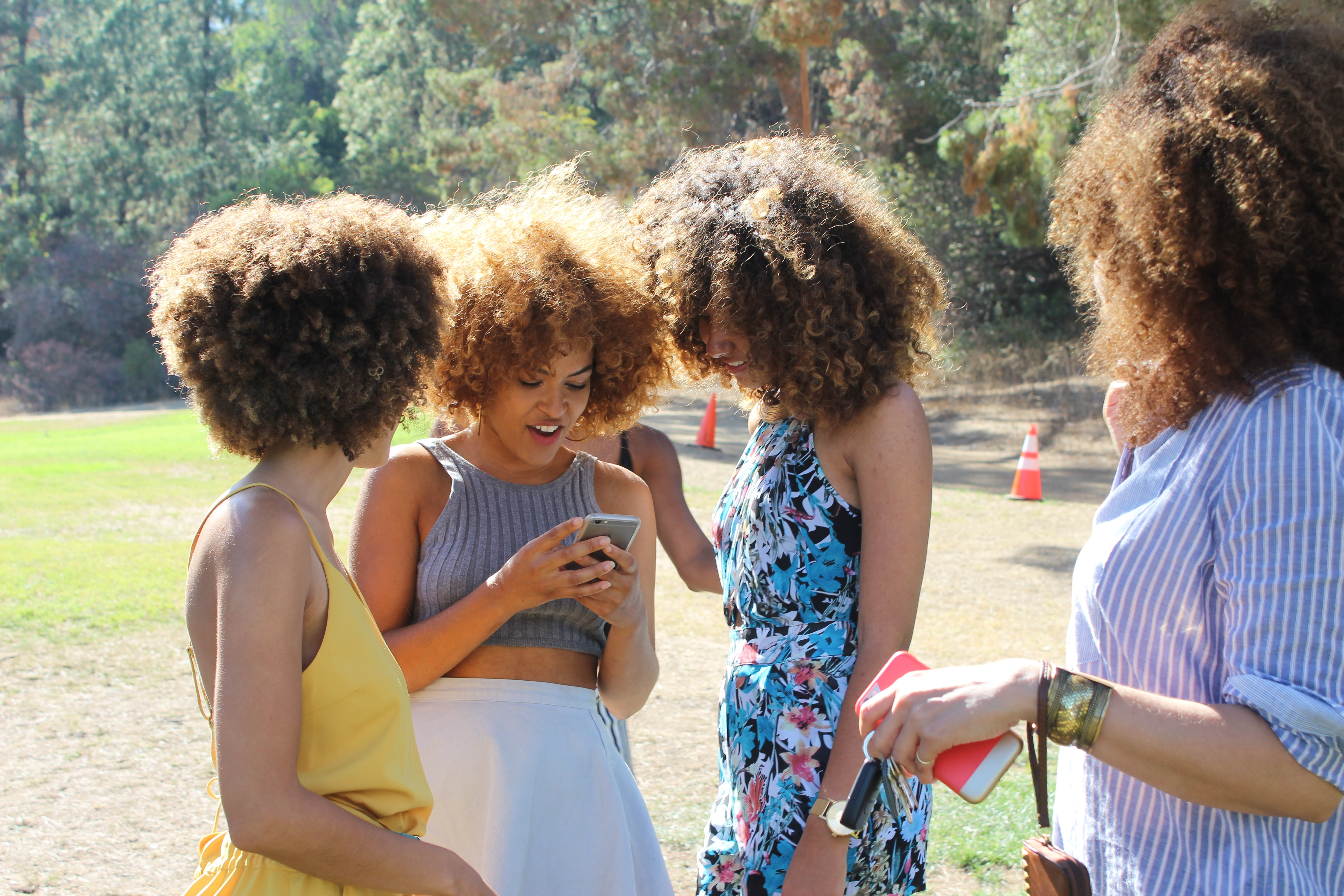 A photo featuring several women with curly hair standing together.