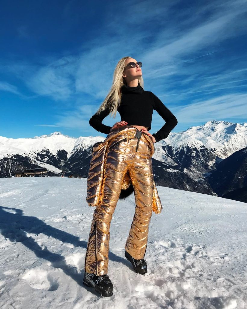 An influencer stands on a snow-covered mountain.
