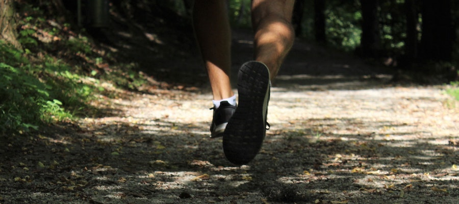A close-up of a trail runner's legs and shoes, by Tara Glaser.