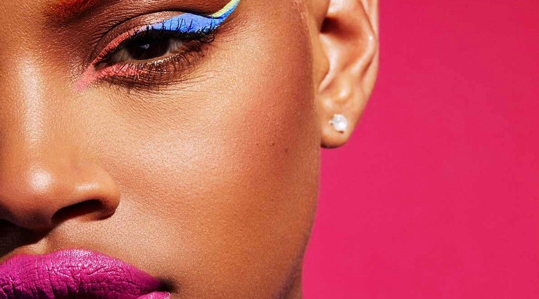 A model shows off a colorful makeup look created with Fenty Beauty products.