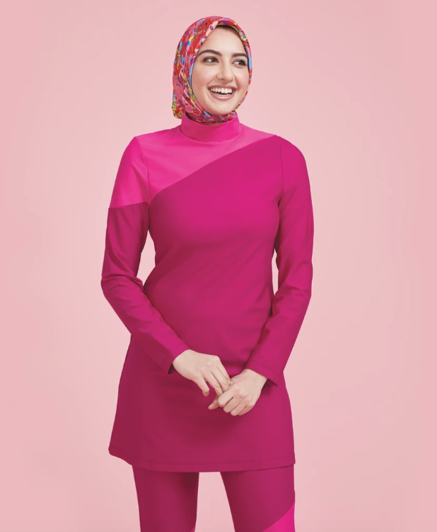 A woman wearing a hijab models Summersalt's full-coverage swim tunic.
