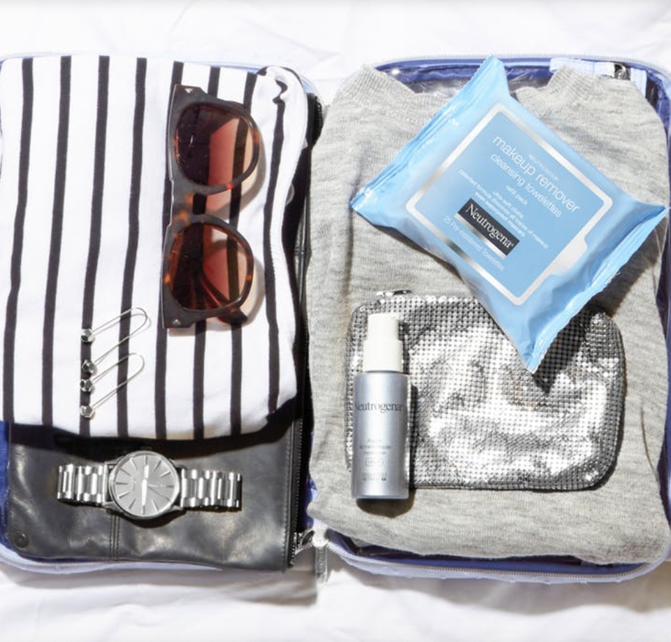 A photo of travel essentials including Neutrogena skincare's Makeup Remover Cleansing Towelettes.