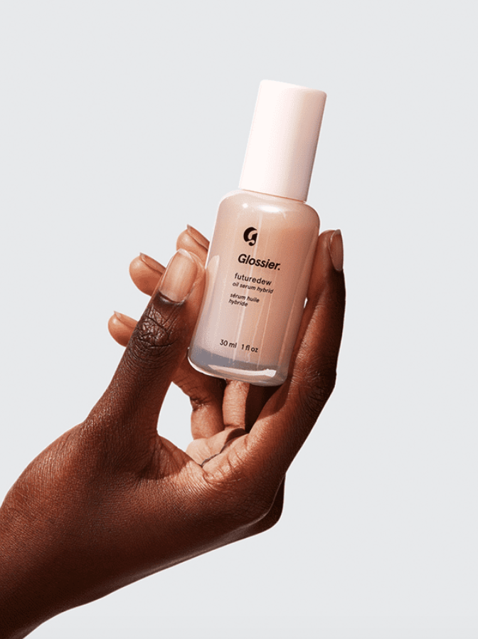 An advertisement photo of a hand holding Glossier skincare's Futuredew.