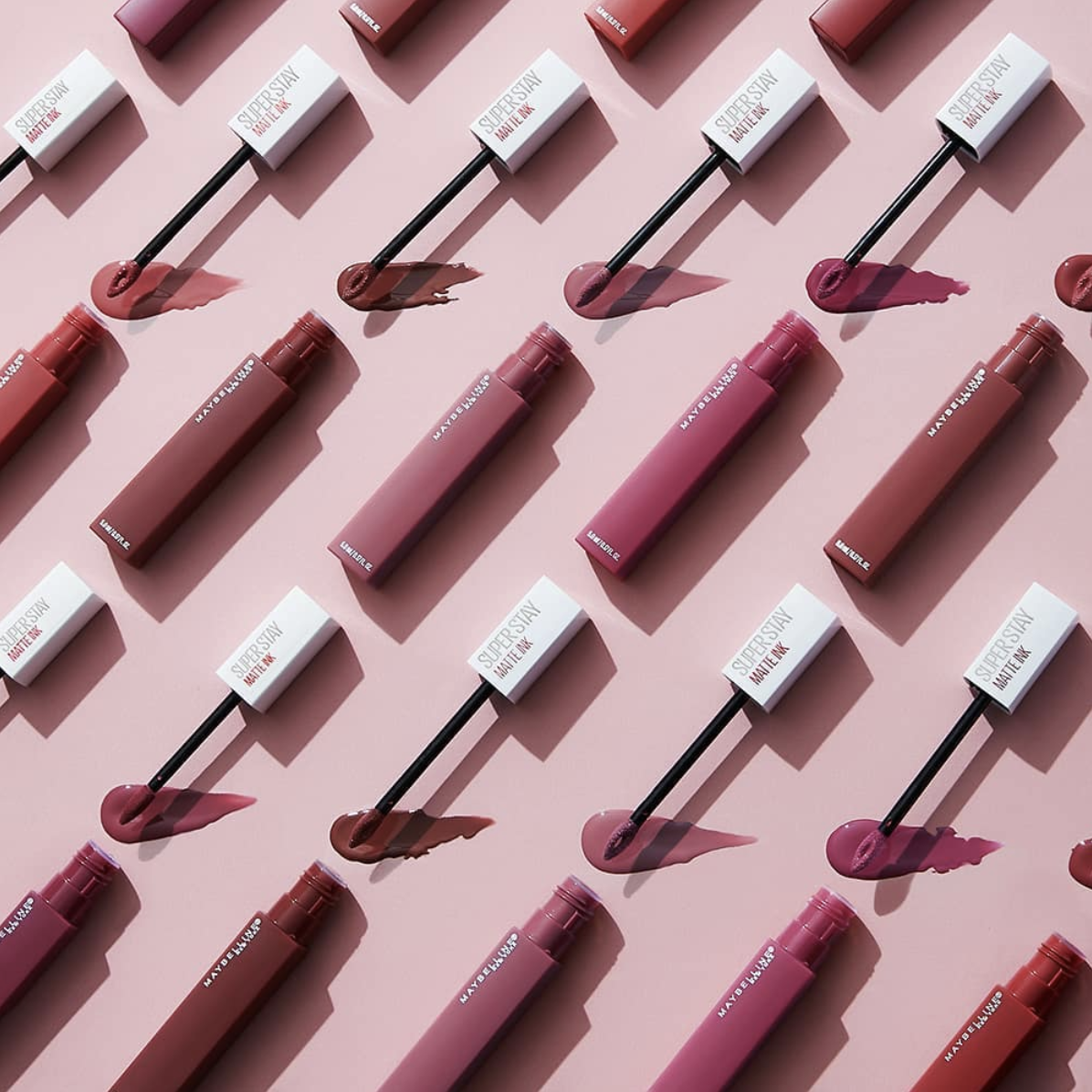 A geometric flat-lay featuring several shades of Maybelline's SuperStay Matte Ink Liquid Lipstick.