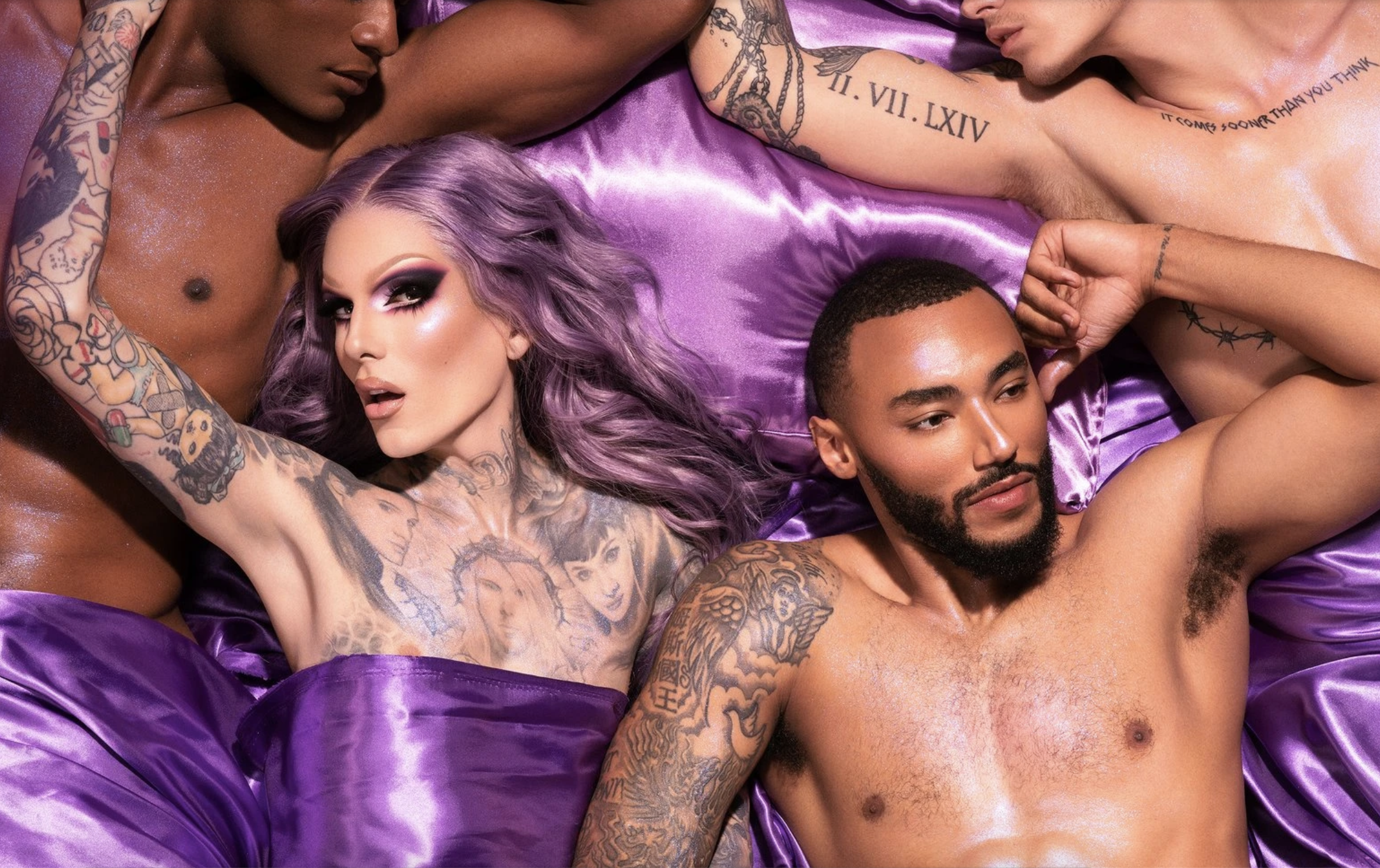 An advertisement for Jeffree Star Cosmetics' Blood Lust Collection, featuring Jeffree Star himself laying with scantily clad men on a purple silk sheet.